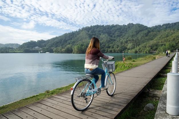 Jovem, mulher, bicicleta equitação, ligado, sol, lua, lago, bicicleta, rastro