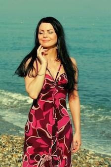Jovem mulher bonita à beira-mar no verão
