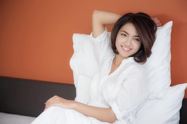 Jovem mulher bonita acordando alegremente, depois de uma boa noite de sono