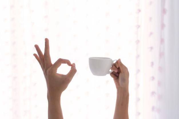 Jovem mulher bonita acordando de manhã na cama, esticando os braços com uma xícara de café e mostrando sinal okey.