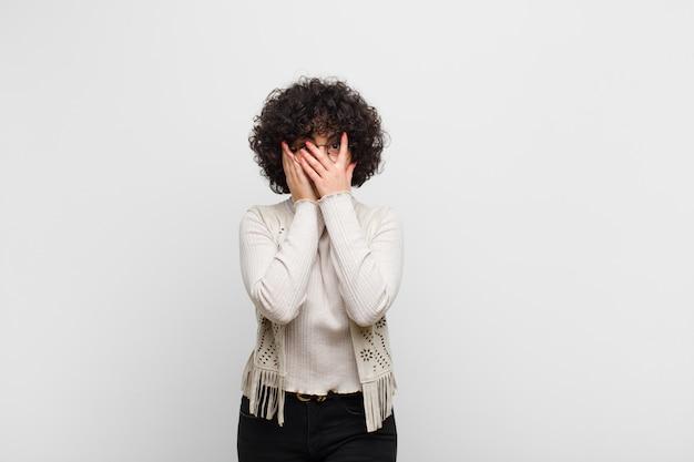Jovem mulher bonita afro sentindo medo ou vergonha, espiando ou espionando com os olhos semicobertos com as mãos