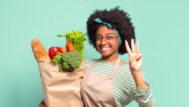 Jovem mulher bonita afro sorrindo e parecendo amigável, mostrando o número dois ou o segundo com a mão para a frente