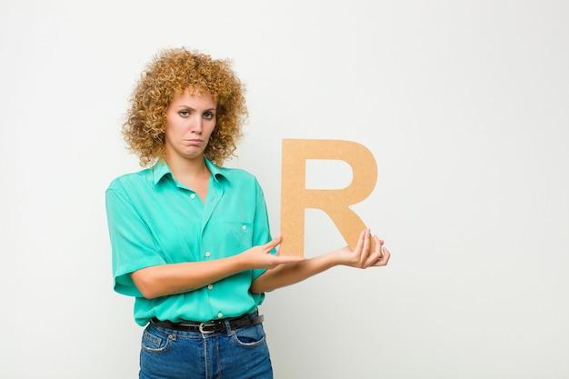 Jovem mulher bonita afro, triste, deprimida, infeliz, segurando a letra r do alfabeto para formar uma palavra ou frase.