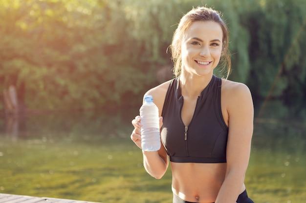 Jovem mulher bonita água potável durante a manhã jogging no parque