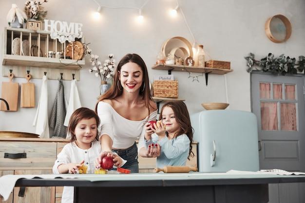 Jovem mulher bonita alimenta dois filhos com maçãs enquanto eles sentados perto da mesa com brinquedos