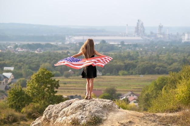 Jovem mulher bonita americana com cabelo comprido, segurando acenando na bandeira do vento eua em seus sholders em pé ao ar livre, aproveitando o dia quente de verão.