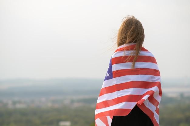Jovem mulher bonita americana com cabelo comprido, segurando acenando na bandeira dos eua do vento em seus sholders em pé ao ar livre, aproveitando o dia quente de verão.