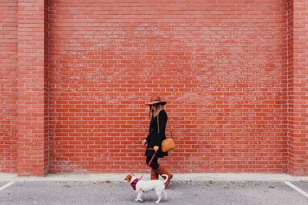 Jovem mulher bonita andando com seu cachorro na rua. parede de tijolos laranja. amor e animais de estimação ao ar livre.