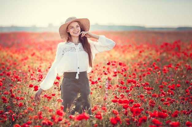 Jovem mulher bonita andando e dançando por um campo de papoulas, verão ao ar livre. tonificado.