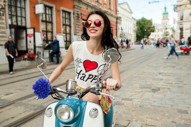 Jovem mulher bonita andando na rua da cidade de moto