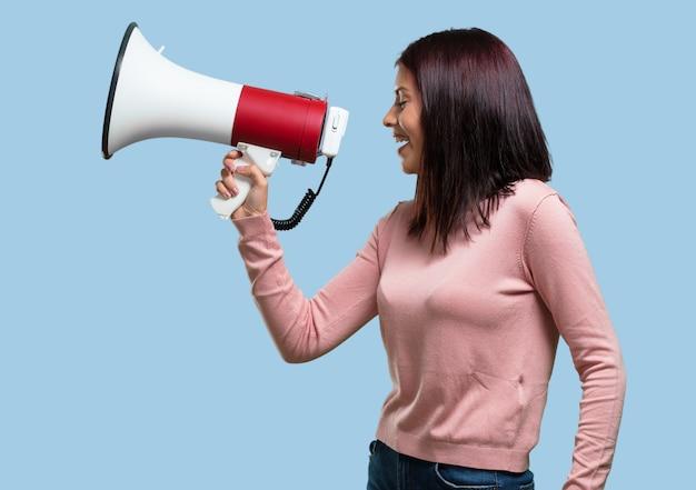 Jovem mulher bonita animada e eufórica, gritando com um megafone