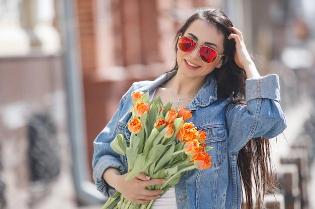 Jovem mulher bonita ao ar livre em tempo de primavera. retrato de menina atraente perto. senhora segurando presentes, caixas de presentes. mulher com flores. alegre mulher segurando tulipas.