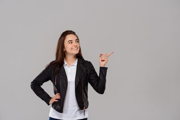 Jovem mulher bonita, apontando o dedo no lado ao longo da parede roxa