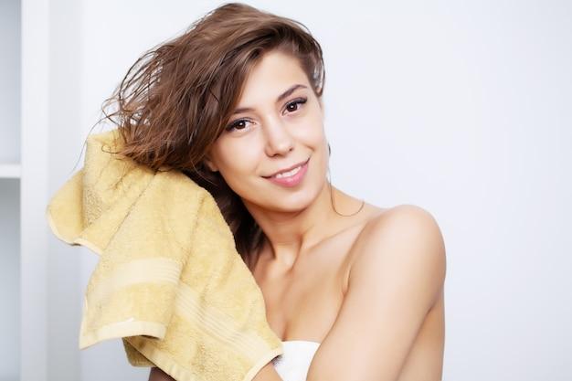 Jovem mulher bonita após tratamentos de spa para cuidar dos cabelos limpa o cabelo com uma toalha