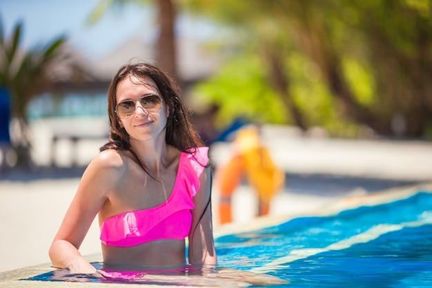 Jovem mulher bonita aproveitando as férias de verão na piscina de luxo
