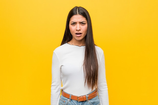 Jovem mulher bonita árabe contra amarelo gritando muito irritado e agressivo.