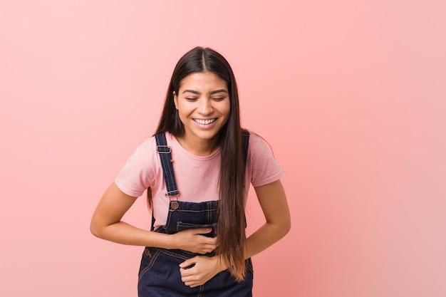 Jovem mulher bonita árabe vestindo um jeans dungaree ri alegremente e se diverte mantendo as mãos no estômago.