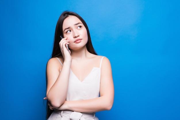 Jovem mulher bonita asiática falando no celular, isolada sobre a parede azul