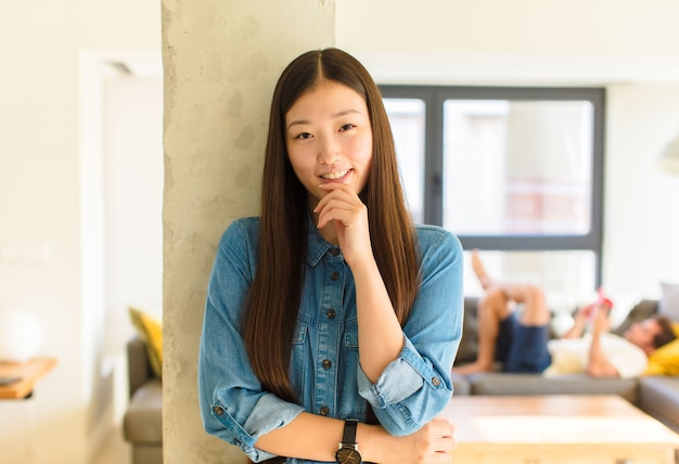 Jovem mulher bonita asiática parecendo feliz e sorrindo com a mão no queixo, pensando ou fazendo uma pergunta, comparando opções