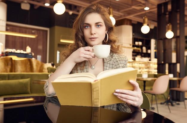 Jovem mulher bonita bebe café e livro de leitura no café