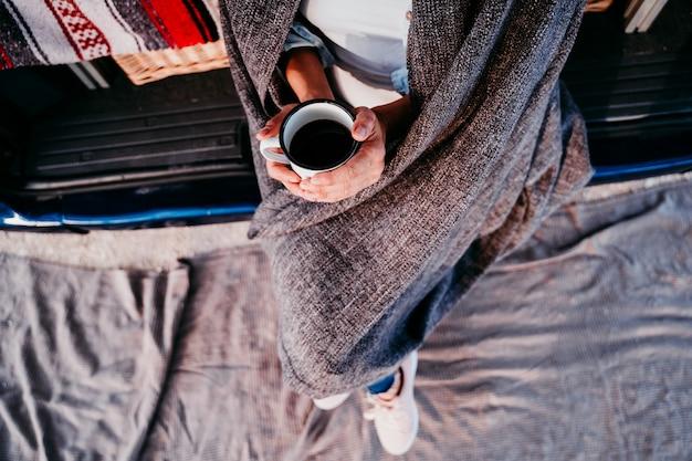 Jovem mulher bonita bebendo café ou chá acampar ao ar livre com uma van. conceito de viagens. vista do topo