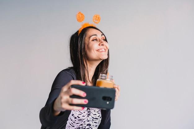 Jovem mulher bonita bebendo suco de laranja e tomando uma selfie com telefone móvel. vestindo uma fantasia de esqueleto preto e branco. conceito de dia das bruxas. interior