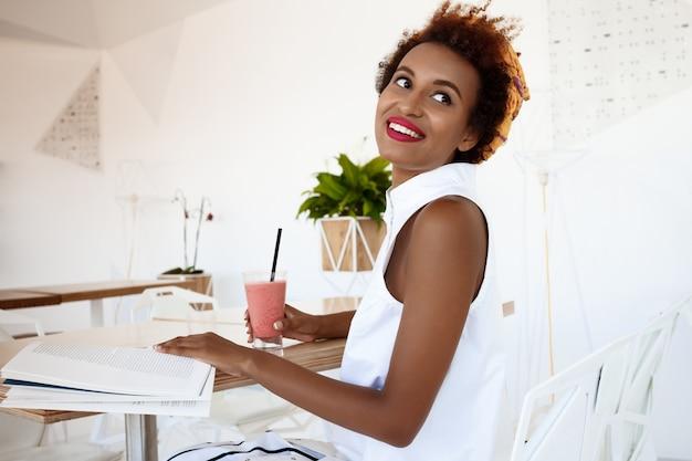 Jovem mulher bonita bebendo suco sorrindo descansando no café