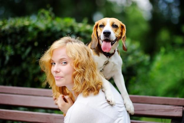 Jovem mulher bonita brincando com cachorro beagle no parque de verão