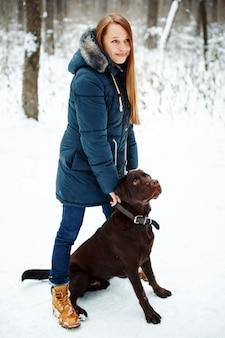 Jovem mulher bonita brincando com seu cachorro
