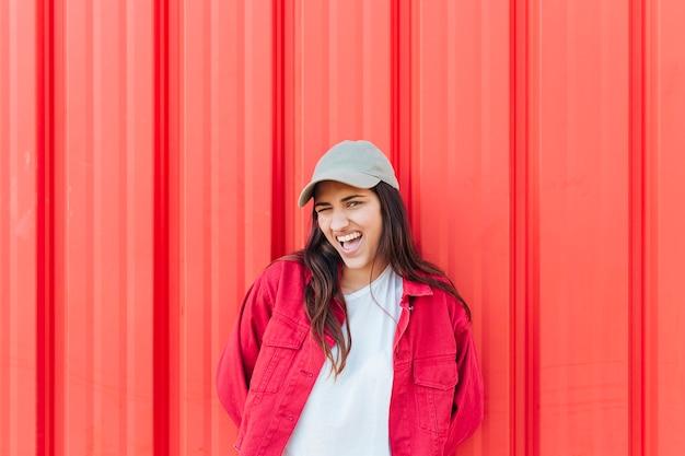 Jovem mulher bonita brincando na frente do pano de fundo de metal vermelho brilhante