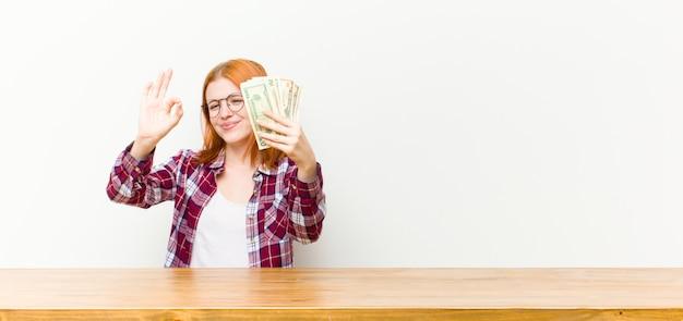 Jovem mulher bonita cabeça vermelha na frente de uma mesa de madeira com notas de dólar