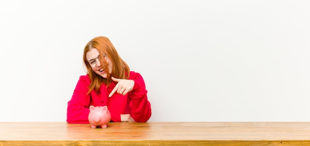Jovem mulher bonita cabeça vermelha na frente de uma mesa de madeira com um cofrinho