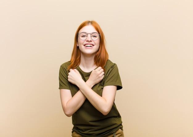 Jovem mulher bonita cabeça vermelha sorrindo alegremente e comemorando, com os punhos cerrados e braços cruzados, sentindo-se feliz e positivo