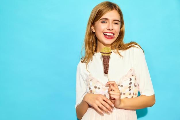 Jovem mulher bonita cantando com adereços microfone falso. mulher na moda em roupas de verão casual. modelo engraçado isolado na parede azul