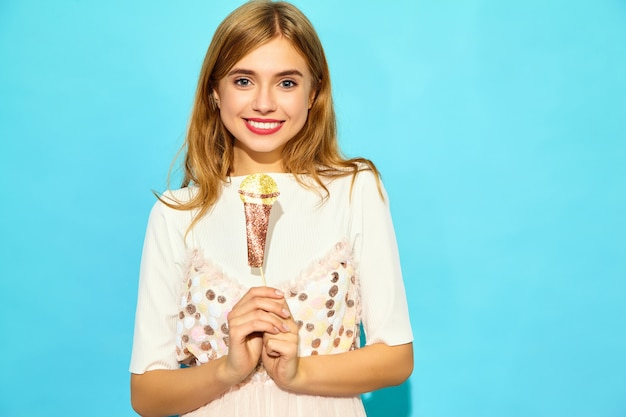 Jovem mulher bonita cantando sua melhor música com microfone falso de adereços. mulher na moda em roupas de verão casual. modelo engraçado isolado na parede azul