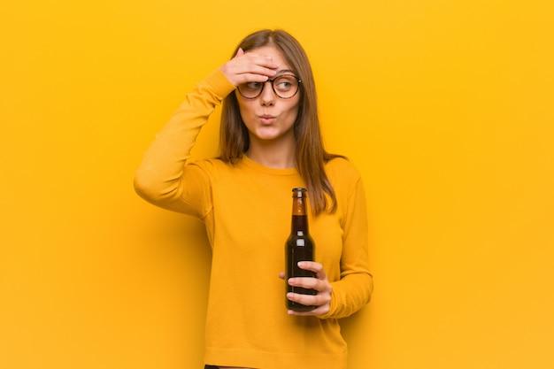 Jovem mulher bonita caucasiana preocupada e oprimida. ela está segurando uma cerveja.