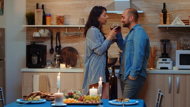 Jovem mulher bonita caucasiana seduzindo o homem durante o jantar festivo. casal adulto tendo encontro romântico em casa, na cozinha, bebendo vinho tinto, conversando, sorrindo, apreciando a refeição na sala de jantar