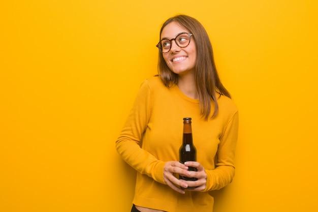 Jovem mulher bonita caucasiana sorrindo confiante e cruzando os braços, olhando para cima. ela está segurando uma cerveja.