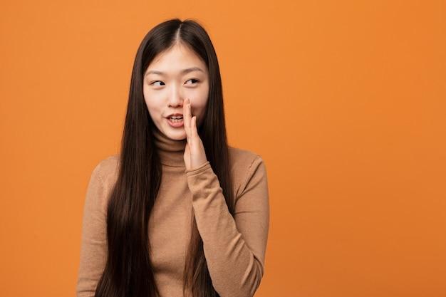 Jovem mulher bonita chinesa está dizendo uma notícia secreta sobre frenagem quente e olhando de lado