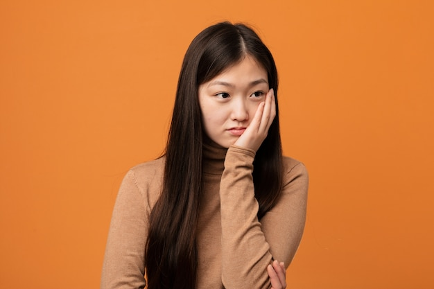 Jovem mulher bonita chinesa que está entediada, cansada e precisa de um dia de relaxamento.