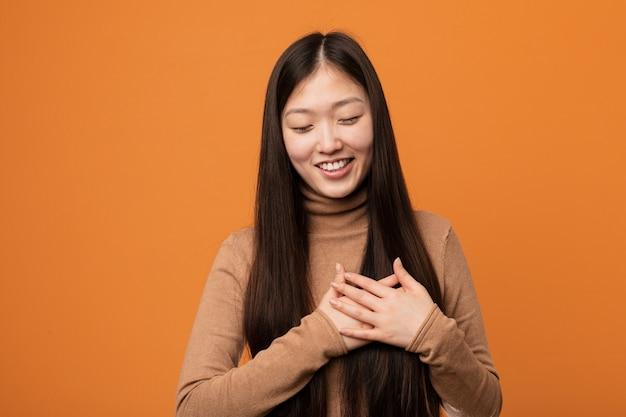 Jovem mulher bonita chinesa rindo mantendo as mãos no coração