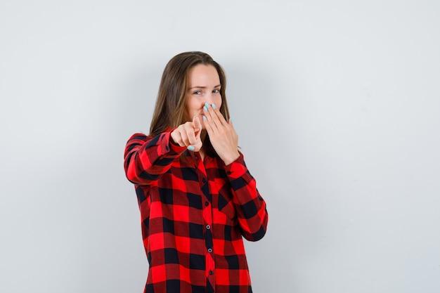 Jovem mulher bonita com a mão na boca, apontando para a câmera em uma camisa casual e parecendo feliz. vista frontal.
