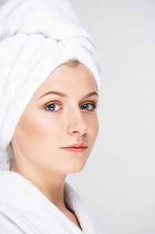 Jovem mulher bonita com a pele perfeita em toalha de banho