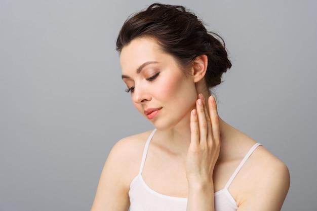 Jovem mulher bonita com a pele perfeita tocando seu rosto, cosmetologia, beleza e conceito de spa