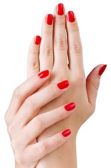 Jovem mulher bonita com as mãos com manicure vermelha