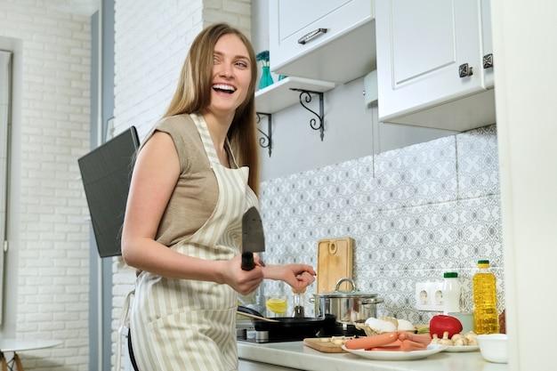 Jovem mulher bonita com avental em pé na cozinha com faca cortando comida
