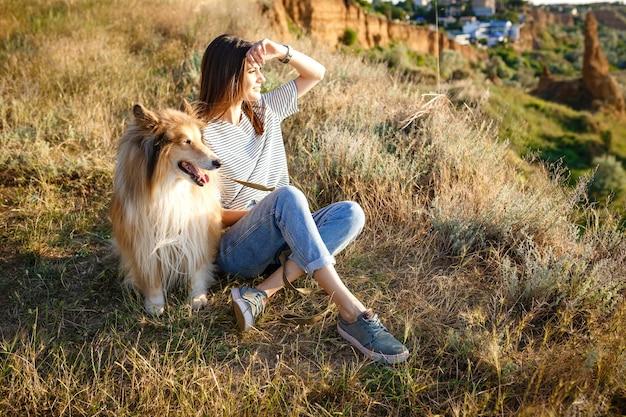 Jovem mulher bonita com cabelo comprido, andando com cachorro collie. ao ar livre no parque. perto do mar, verão beatch