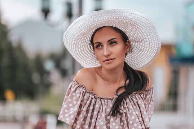 Jovem mulher bonita com cabelo comprido em chapéu branco e vestido begie andando em uma cidade