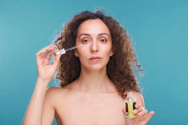 Jovem mulher bonita com cabelo comprido ondulado escuro aplicando soro rejuvenescedor no rosto enquanto segura um pequeno frasco e uma pipeta