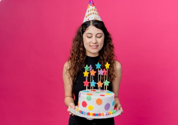 Jovem mulher bonita com cabelo encaracolado com um boné de férias segurando um bolo de aniversário feliz e conceito de festa de aniversário positivo sobre rosa